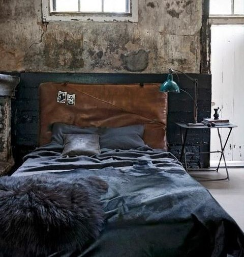 a cool industrial bedroom with shabby chic walls, a leather upholstered bed, a metal lamp and table and dark bedding
