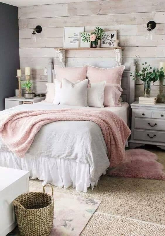 a cozy farmhouse bedroom with a whitewashed wooden wall and whitewashed furniture, pink bedding, greenery and a basket for storage