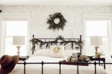 a cozy farmhouse bedroom with white brick walls, fir branches and a forged bed looks serene and chic