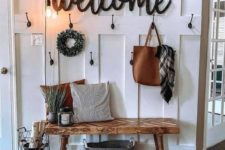 a cozy farmhouse entry with a jute rug, a wooden bench, a sign, bulbs and a wreath plus some candle lanterns