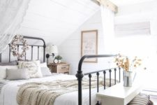 a cozy farmhouse space with a forged bed in a niche, a white bench, some baskets and a wooden beam with lace curtains