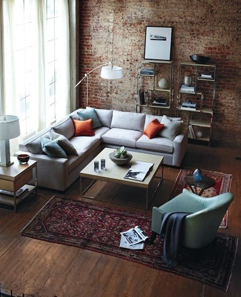 a cozy industrial living room with a red brick wall, a wooden floor, boho rugs, neutral furniture and metal shelving units