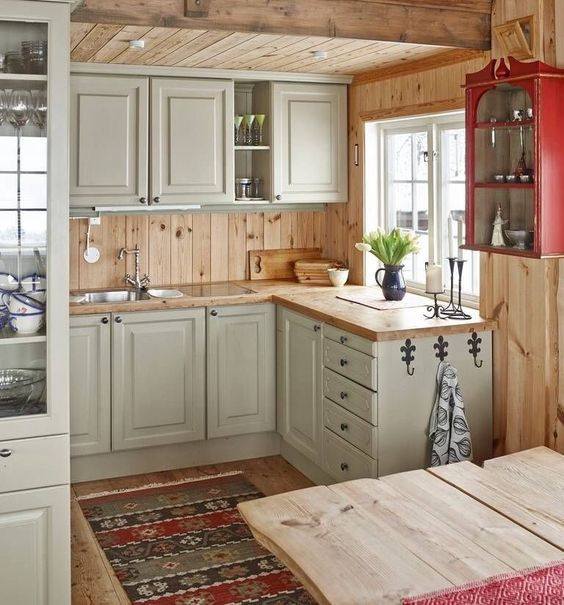 a cozy rustic kitchen in light grey, with wooden countertops and a backsplash plus a wooden kitchen island is very welcoming
