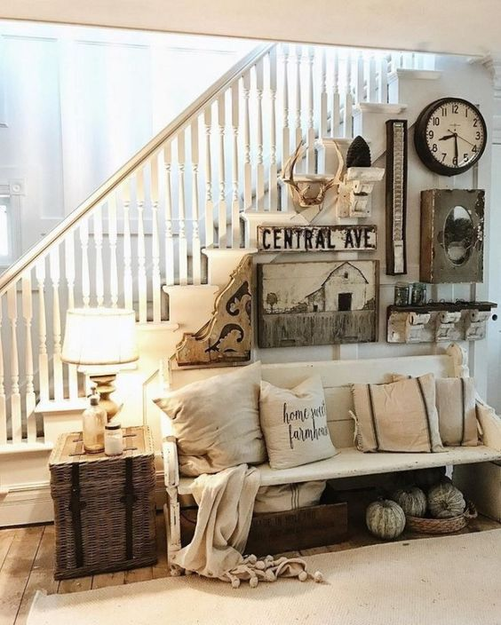 a cozy vintage farmhouse entryway with a wooden bench, pillows, a gallery wall with lots of different items and a woven box plus a lamp