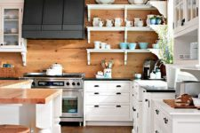 a cozy white rustic kitchen with a wooden backsplash, touches of black for drama and some wooden furniture