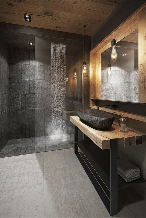 a creative grey bathroom done with grey tiles, a wood and metal vanity, a stone sink and a large lit up mirror