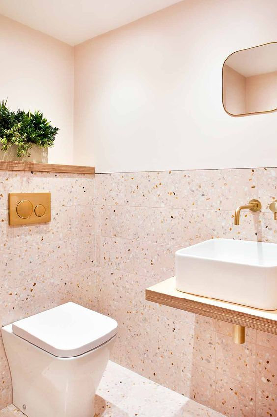 a cute blush bathroom with painted and terrazzo tile walls, white appliances and gold fixtures looks pretty, cute and very chic