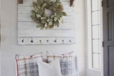 a cute farmhouse space with a wooden sign with a wreath, a selection of pumpkins and baskets, a white bench with pillows