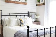 a cute modern farmhouse bedroom with white wooden plank walls, a forged bed, a sphere chandelier, shelves and greenery