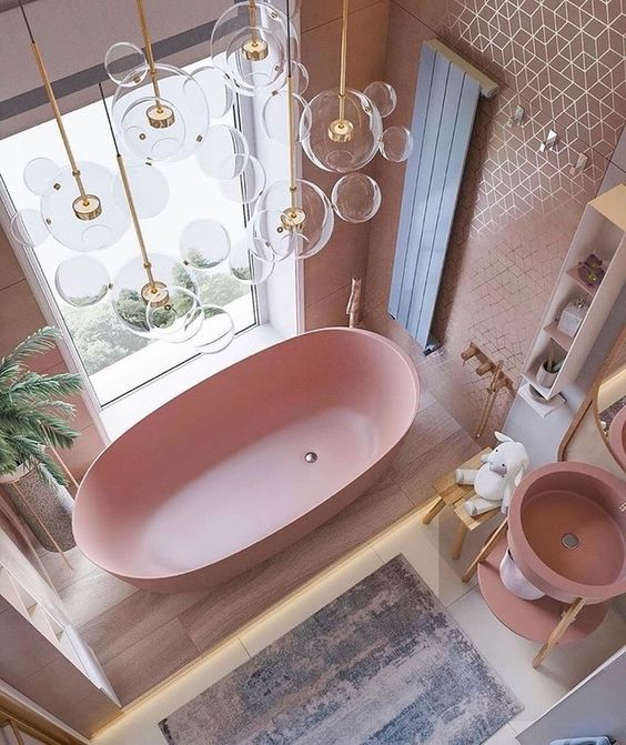 a cute pink bathroom with a pink bathtub, sink, tiled walls and touches of gold here and there