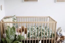 a cute tropical nursery with potted greenery, wooden furniture, a jute rug, baskets with toys and pretty artworks