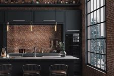 a dark minimalist meets industrial kitchen with black cabinets and cocnrete countertops, pendant lamps and metal stools