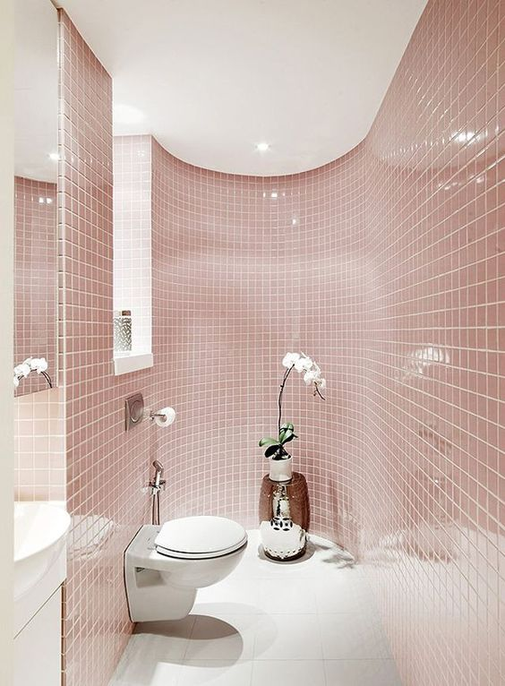 a delicate blush bathroom all clad with tiles, with a window, white appliances and a potted orchid for a touch of luxury
