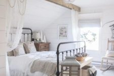 a dreamy farmhouse bedroom with a wooden beam and curtains on it, with a wooden candle lantern, some baskets and pretty bedding