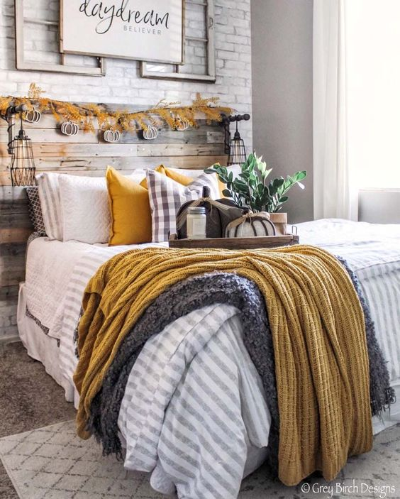a fall farmhouse bedroom with a wooden bed, a brick wall, pumpkin garlands, colorful bedding and a sign on the wall