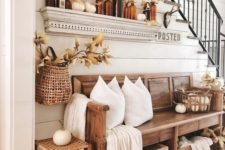 a fall farmhouse entryway with a wooden bench, a woven stool, pillows and a blanket, amber bottles and lots of leaves