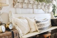 a farmhouse ebtryway with a shabby chic bench, a basket with clocks, pillows and blankets, a shelf with greenery and vintage mirrors