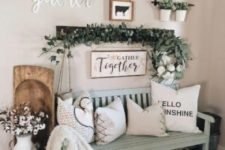 a farmhouse entry with a gallery wall, some greenery, a cotton arrangement, pillows on a mint bench and baskets
