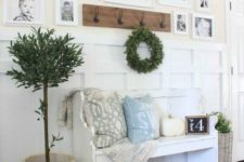 a farmhouse entryway with a white bench with pillows, a pumpkin, a gallery wall, a greenery wreath and a potted tree