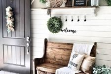 a farmhouse entryway with a wooden bench, candle lanterns, signs, blooms and greenery and a large mirror