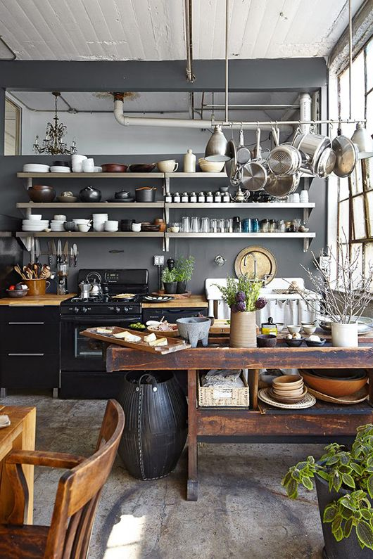 a farmhouse meets industrial kitchen with grey walls, black metal cabinets, a shabby wooden kitchen island and exposed pipes