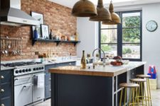a farmhouse meets industrial kitchen with red brick walls, grey cabinets with stone countertops, vintage lamps and stools