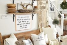 a farmhouse meets woodland entryway with a wooden bench, some crates and baskets, open shelving, antlers and branches