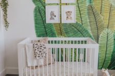 a fun tropical nursery with a painted leaf wall, pretty artworks, toys in baskets and a faux fur rug