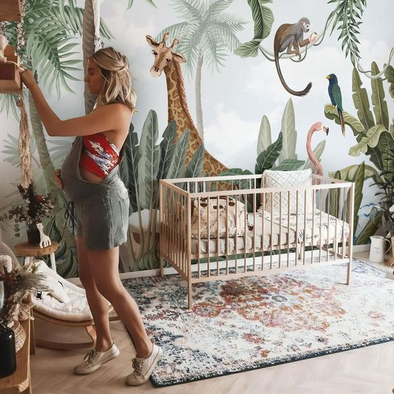 a fun tropical nursery with creative jungle wallpaper, a printed rug, boho pillows, neutral furniture and potted greenery