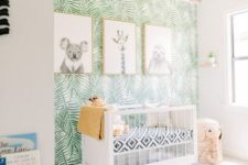 a funny tropical nursery with a tropical leaf print wall, black and white artworks, an elephant basket and a sphere chandelier