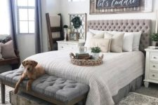 a gorgeous farmhouse bedroom with an upholstered bed and bench, with touches of reclaimed wood and greenery