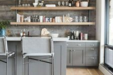 a gorgeous farmhouse kitchen with grey cabinets, open industrial shelving and a reclaimed wooden backsplash looks chic