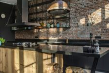 a gorgeous industrial kitchen with red brick walls, black cabinets, a large wooden kitchen island and a vintage lamp