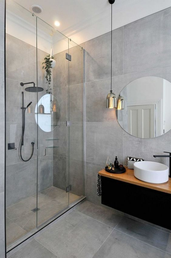 a gorgeous minimalist grey bathroom with large scale tiles, a pendant lamp and a floating vanity with a sink