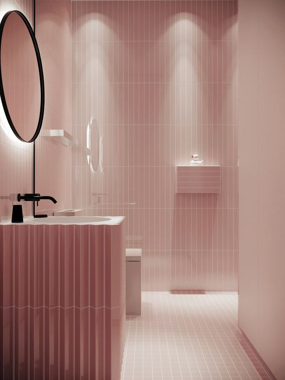 a gorgeous pink bathroom all clad with tiles, with floating elements and black touches for drama