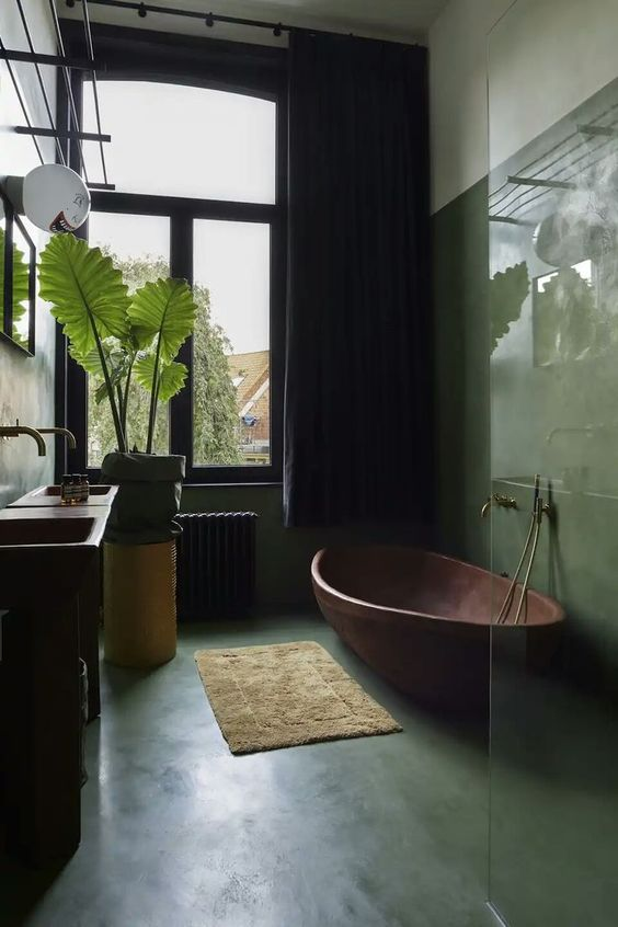 a gorgeous tropical bathroom with green walls and a floor, a copper tub, potted plants and a glass enclosed shower