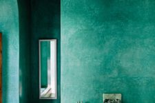 a green Moroccan-style bathroom with everything of concrete and plaster, with a small mirror and built-in tub