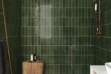 a green bathroom clad with long and narrow tiles, with gold and brass touches and a tree stump stool in the shower