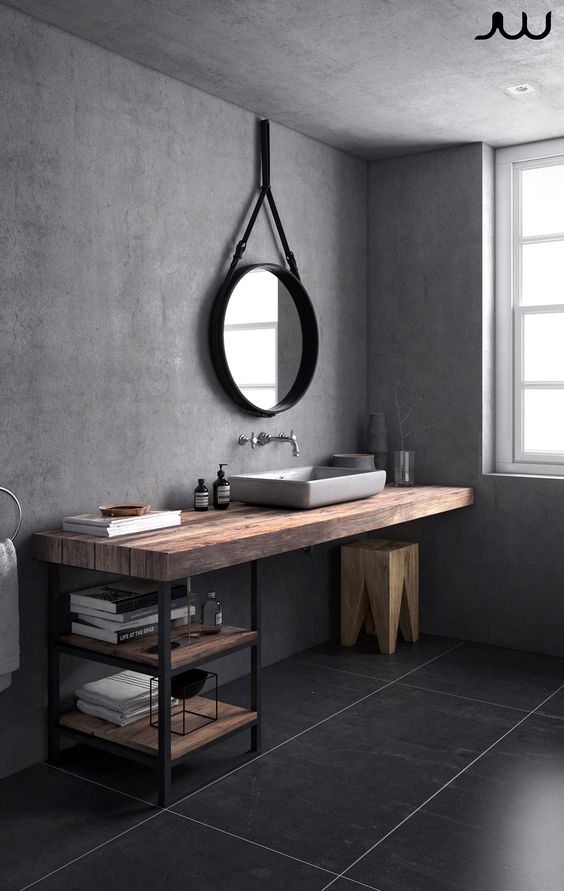a grey Scandinavian bathroom with dark tiles on the floor, concrete walls, an industrial vanity, black fixtures