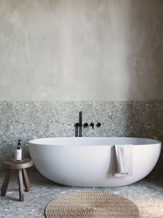 a grey bathroom done with stone and plaster, with a free standing tub, a wooden stool and a jute rug