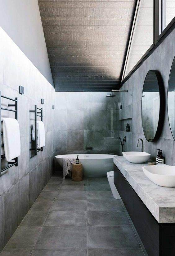 a grey bathroom with an attic ceiling, white appliances, a black and grey vanity and black fixtures