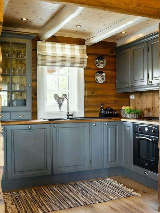 a grey farmhouse kitchen with wooden countertops and a backsplash, with plaid shades is very chic and cool