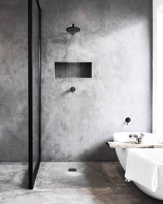 a grey minimalist bathroom done with concrete, with black fixtures and a wooden cuddy on the bathtub