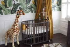 a jungle nursery with a tropical leaf wall, a dark crib, a mustard canopy, a fun rug and a toy giraffe