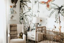 a jungle themed nursery with a fun printed wall, tropical bedding, a leather ottoman, cute jungle themed toys