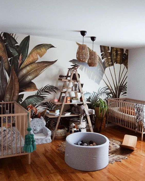 a jungle themed nursery with a printed leaf wall, rattan lamps, an elephant chair and a jute rug