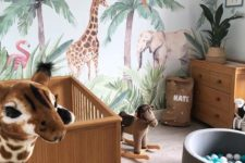 a jungle themed nursery with a statement animal wall, animal toys, potted plants and cute furniture