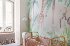 a jungle themed nursery with a statement wall, fun toys, a printed rug and a rattan crib with pastel bedding