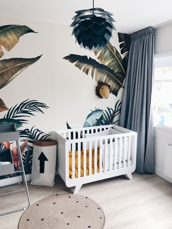 a jungle themed nursery with tropical leaf prints on the wall, a polka dot rug, blue curtains, a unique chandelier and colorful bedding