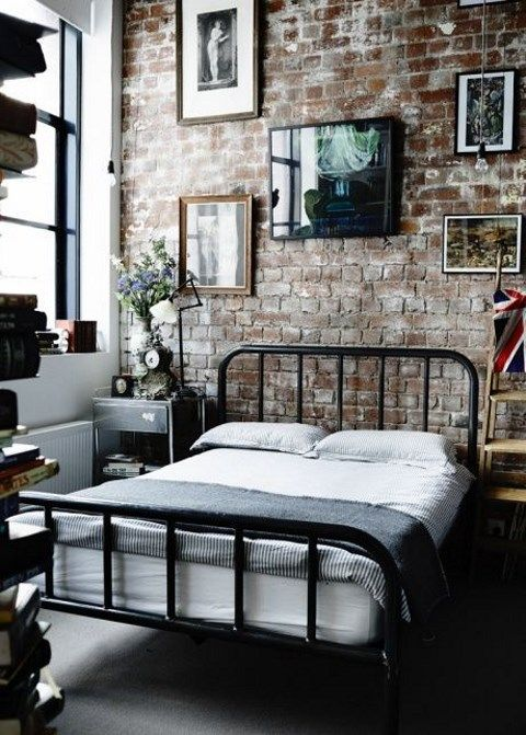 a laconic industrial bedroom with brick walls, a metal bed, mismatching nightstands, a gallery wall and vintage decor